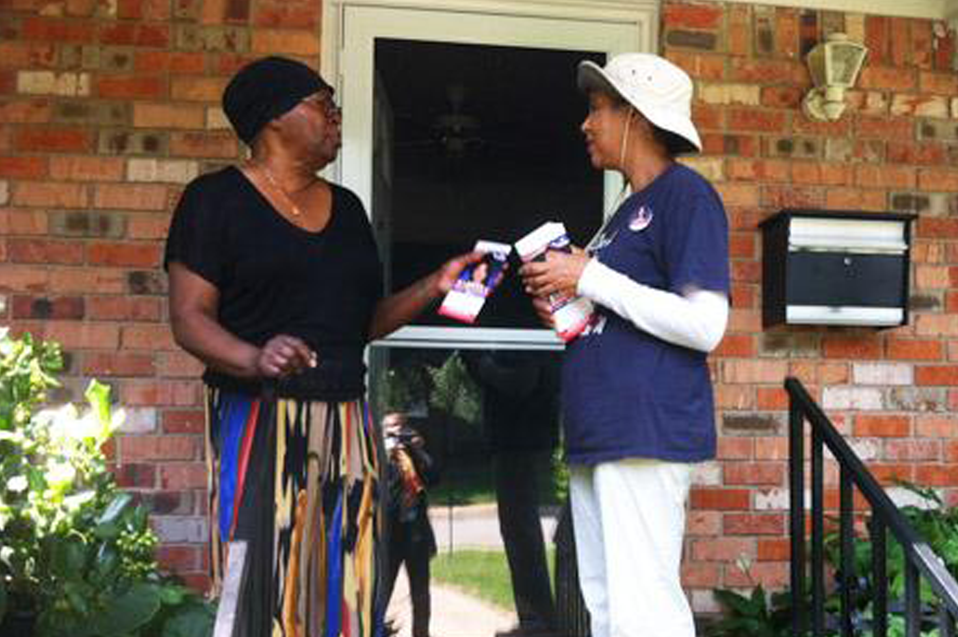 Two people of color talking at a door porch