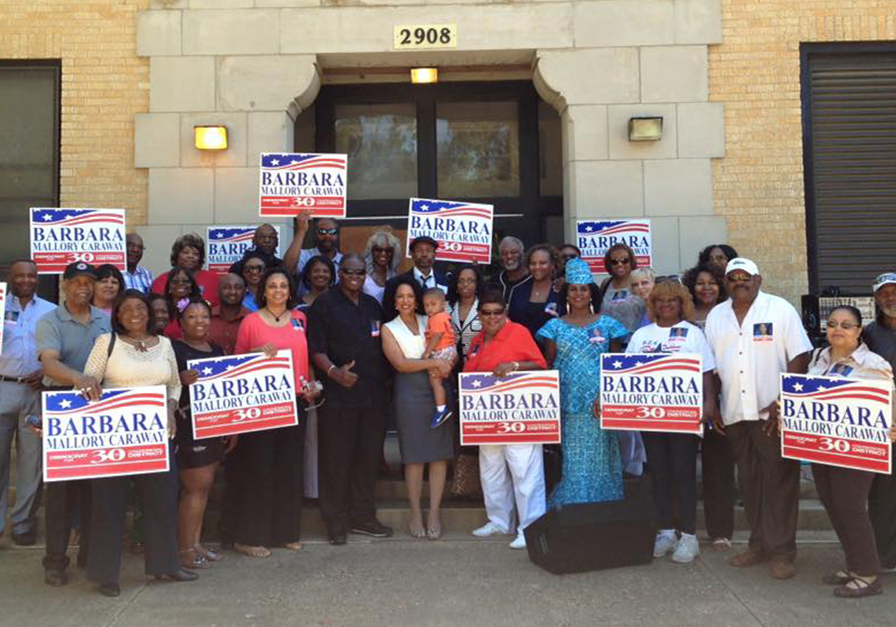 A group of people holding banners in support of Barbara Mallory Caraway